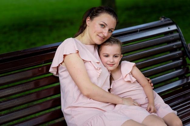 Mère et fille 5-6 ans à pied dans le parc en été, mère embrasse sa fille assise sur un banc, fête des mères