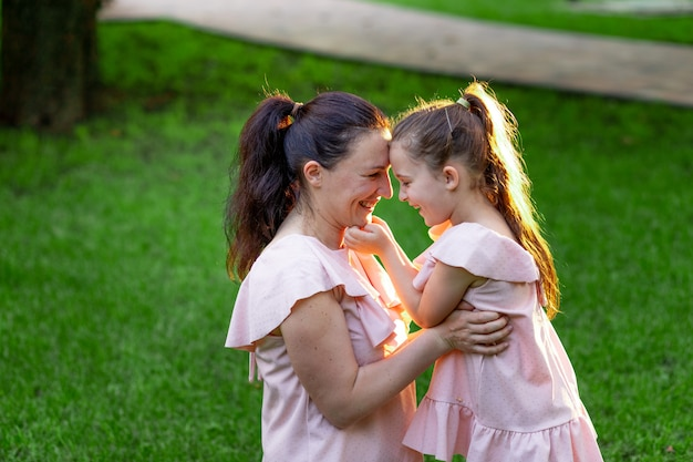 Mère et fille de 5 à 6 ans s'asseoir dans le parc sur l'herbe en été et rire, conversation mère-fille