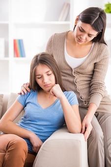 Mère et fille adolescente après une querelle sur le canapé à la maison.