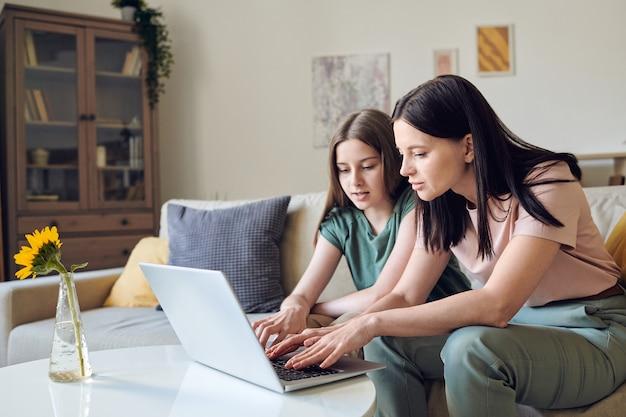 Mère et fille adolescente concentrées vérifiant les boutons de l'ordinateur portable tout en travaillant avec la plate-forme éducative ensemble