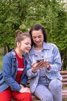Mère et fille adolescente marchant dans un parc, assises sur un banc et regardant dans un smartphone, jeune femme caucasienne heureuse aux cheveux longs et adolescente surfant sur internet à l'extérieur, famille de style de vie