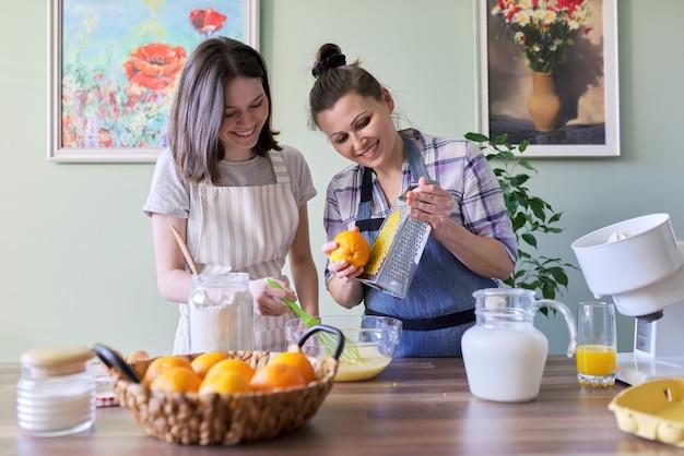 La mère et la fille adolescente préparent des crêpes ensemble à la maison dans la cuisine avec du zeste et du jus d'orange. famille, loisirs, mode de vie, nourriture savoureuse et saine faite maison
