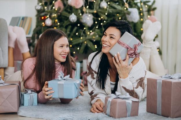 Mère avec fille adulte avec des cadeaux de noël par l'arbre de noël