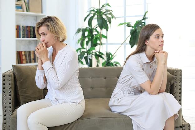Une mère et une fille adulte mécontentes s'assoient dos à dos pour éviter de se parler ou de se regarder, les problèmes de relations familiales entre les parents et les enfants.