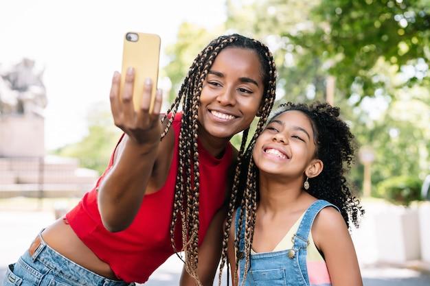 Mère et fille afro-américaine profitant d'une journée à l'extérieur tout en prenant un selfie