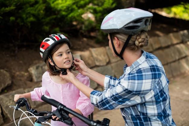 Mère fille aidant à porter un casque de vélo dans le parc