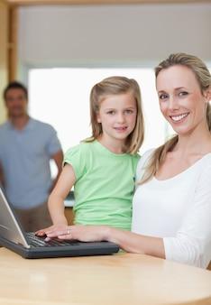 Mère et fille à l'aide de cahier avec le père en arrière-plan
