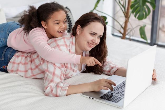 Mère et fille à l'aide de l'ordinateur portable ensemble