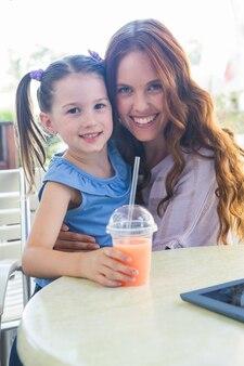 Mère et fille à l'aide de tablette au café terrasse