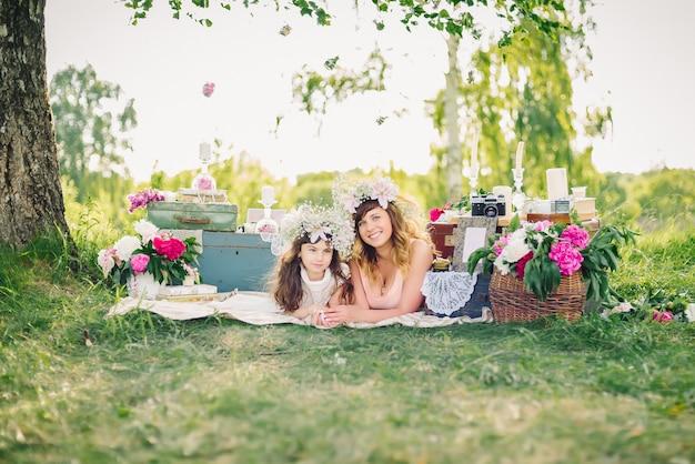 Mère et fille allongée sur une couverture à l'extérieur sur un été ensoleillé