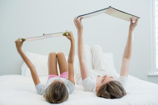 Mère et fille allongée sur le lit et livre de lecture