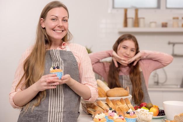 Mère et fille américaines tenant des cupcakes et se souriant