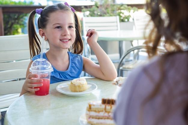 Mère et fille appréciant des gâteaux à la terrasse du café