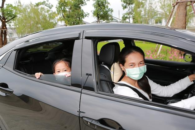 La mère et la fille asiatiques portent un masque d'hygiène allongé dans la voiture en regardant à travers la caméra