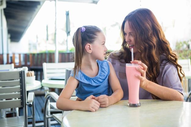 Mère et fille assis devant le café