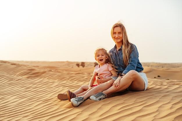 Mère et fille assis ensemble sur une dune de sable dans le désert de dubaï