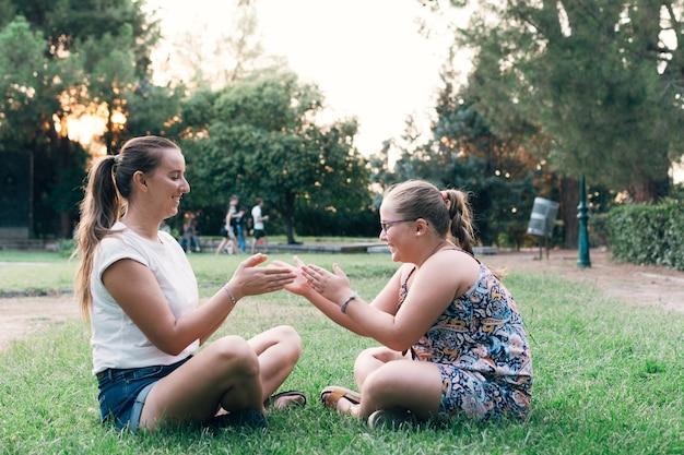 Mère et fille assis ensemble et s'amuser dans un parc.
