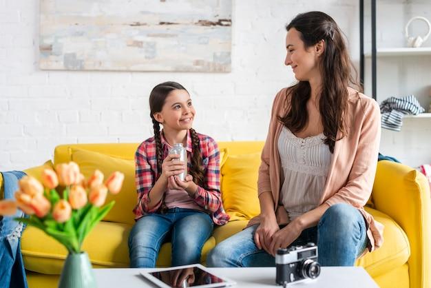 Mère et fille assise sur un canapé jaune