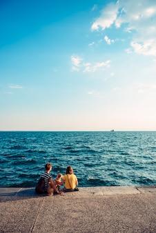 Mère et fille assise sur le front de mer avec chien
