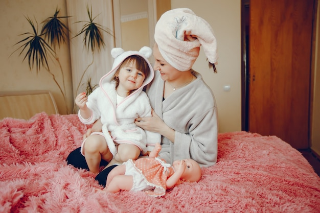 Mère avec fille assise sur un lit