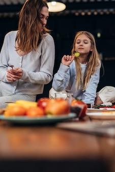 Mère et fille assises sur la table de la cuisine.