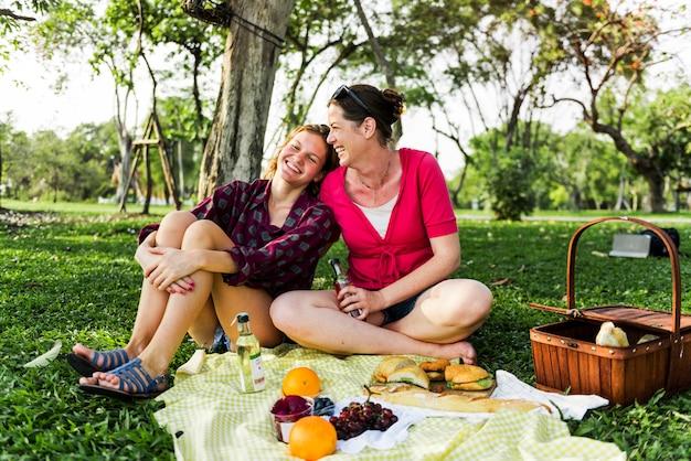 Mère et fille ayant un pique-nique dans le parc