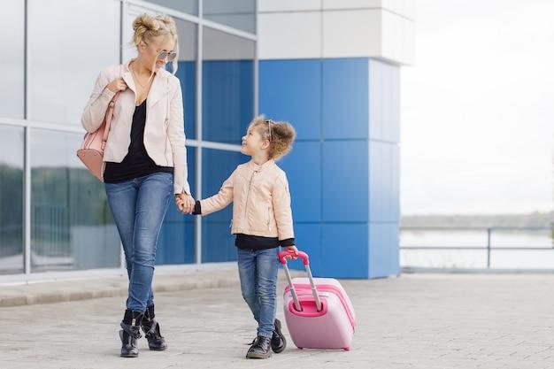 Mère et fille avec des bagages roses en veste rose contre l'aéroport.