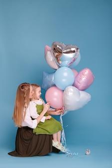 Mère et fille avec des ballons sur une surface bleue. fête des mères