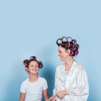 Mère et fille en bigoudis souriant