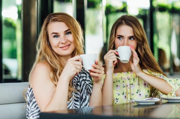 Mère et fille blonde parlent et sourient en buvant du café au lait