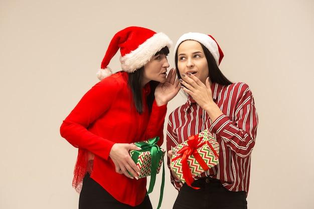 Mère et fille avec bonnet de noel et boîte-cadeau