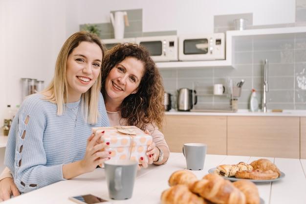 Mère et fille avec un cadeau en regardant la caméra