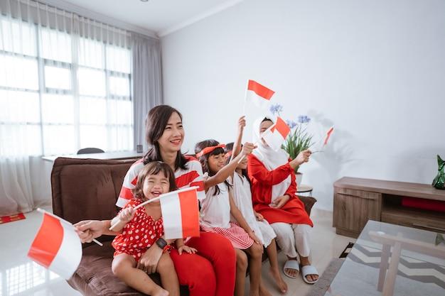 Mère et fille célébrant la fête de l'indépendance indonésienne à la maison en rouge et blanc avec indon...