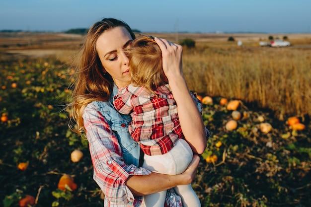 Mère et fille sur un champ avec des citrouilles