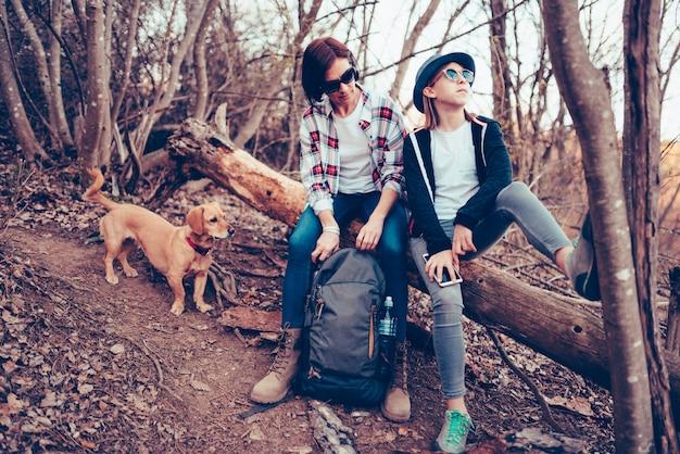 Mère et fille avec chien reposant sur un vieil arbre