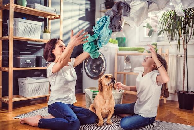 Mère, fille et chien s'amusant à la buanderie