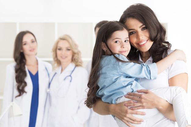 Mère et fille en clinique médicale, équipe de médecins en surface