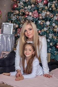 Mère et fille à côté de l'arbre de noël. vacances nouvel an et noël. belle maman et sa fille.