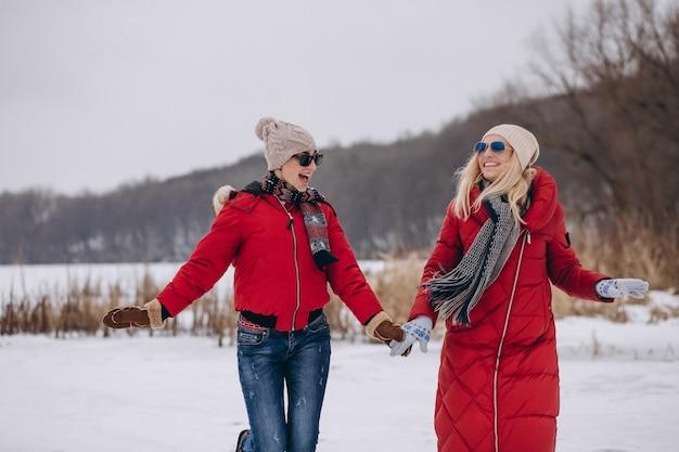Mère et fille courir sur le lac en hiver