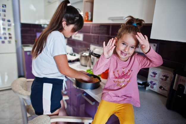 Mère avec fille cuisinant dans la cuisine, moments heureux pour les enfants.