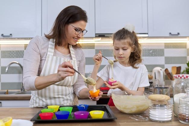 Mère et fille cuisinant des muffins ensemble dans la cuisine à domicile. femme et enfant versant de la pâte crue dans des moules en silicone. fête des mères, famille, cuisine saine faite maison