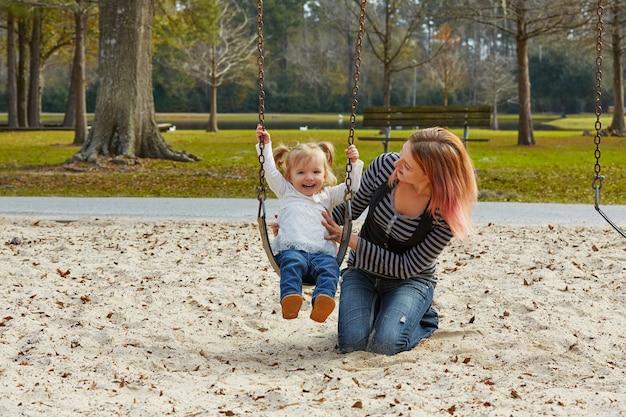 Mère et fille dans une balançoire au parc