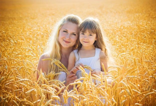 Mère et fille dans un champ de blé. mise au point sélective.