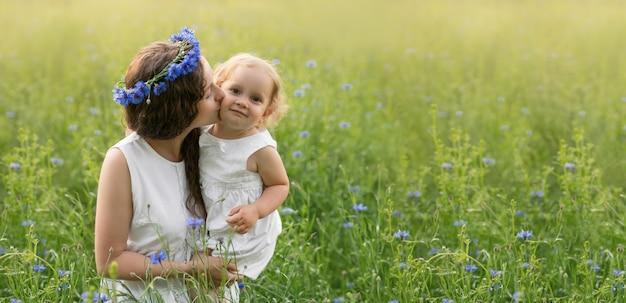 Mère et fille dans un champ de bleuets au coucher du soleil