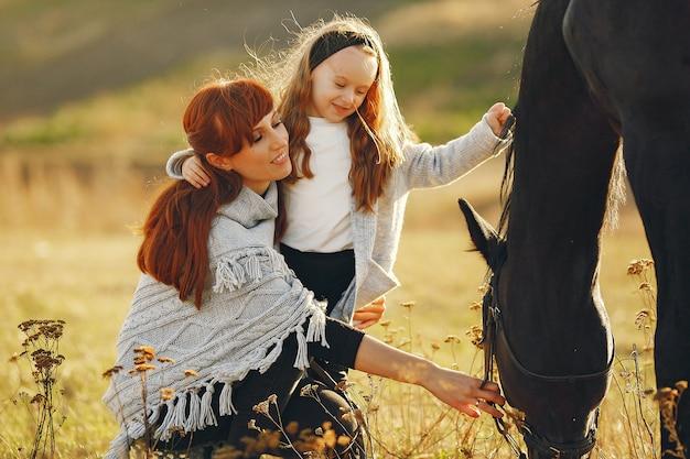 Mère et fille dans un champ jouant avec un cheval