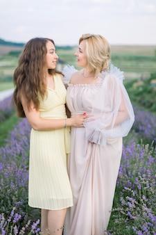 Mère et fille dans un champ de lavande par une belle journée d'été. superbe dame blonde d'âge moyen debout au champ de lavande avec sa jolie jeune fille et profitant de la promenade