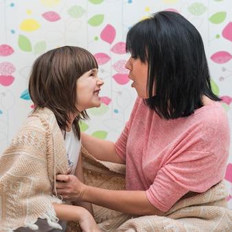 Mère et fille dans une couverture faisant des grimaces