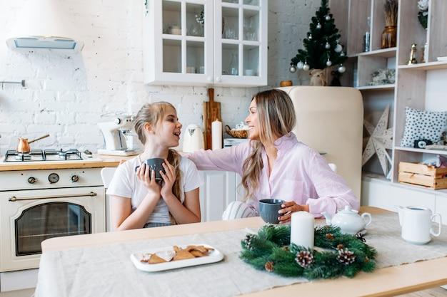 Mère et fille dans la cuisine décorée pour noël et nouvel an, boire du thé ou du cacao, conversation, attendre les invités
