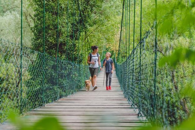 Mère et fille dans la forêt, marchant sur un pont en bois