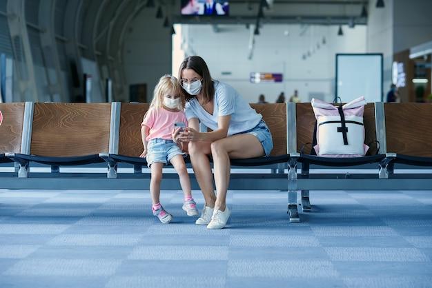 Mère avec fille dans des masques attendant leur vol à l'aéroport femme avec petite fille dedans